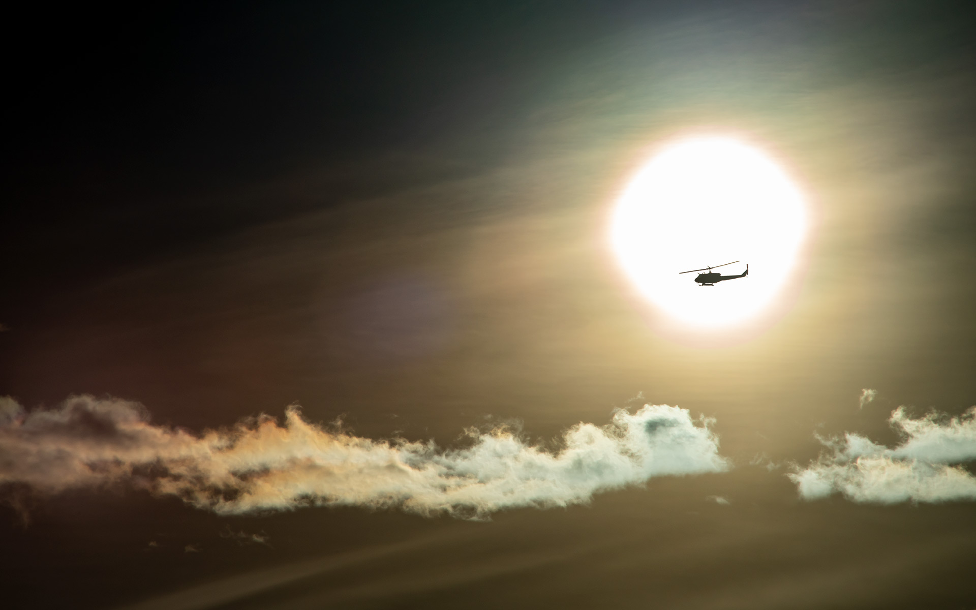 a helicopter in the morning in front of the sun!